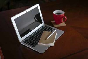 laptop computer and notebook with coffee cup on desk
